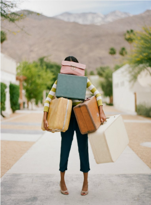 girl holding suitcases, head to toe